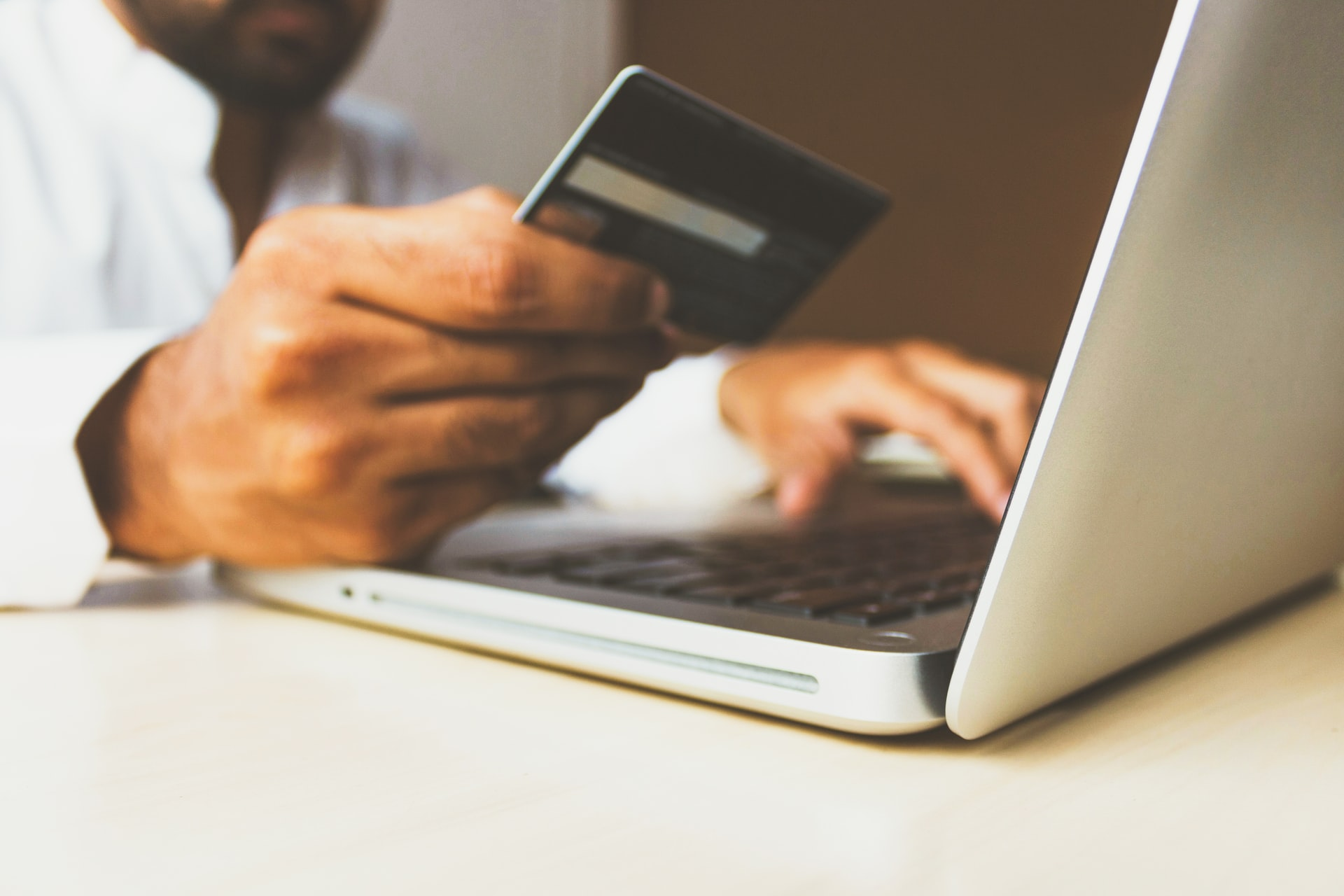 business man on laptop with credit and debit card